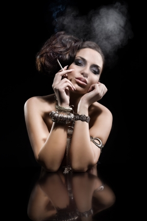 Portrait of beautiful young woman smoking a cigarette  Black background  A lot of jewellery