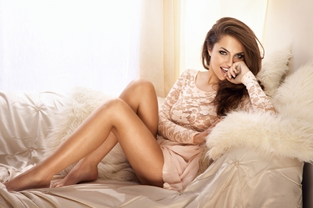 móda: Módní fotografie krásná mladá žena na sobě krajkové šaty, relaxační a usmívající se ve světlé jídelně, na bílém gauči