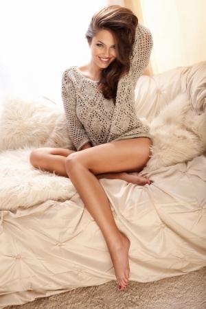 maglioni: Allegro giovane bellezza seduta sul divano in camera luminosa e sorridente, rilassante