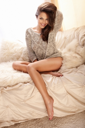 Cheerful young beauty sitting on the couch in bright room and smiling, relaxing photo