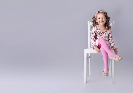 baby chair: Cheerful little girl sitting on the chair with smile, a lot of copy space Stock Photo