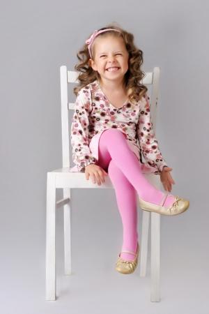 jolie petite fille: Mignon petit enfant assis sur la chaise et souriant portant des v�tements roses