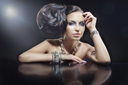 Portrait of beautiful brunette woman wearing jewellery at black mirror table photo