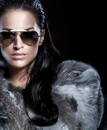 Portrait of beautiful brunette lady wearing fur and sunglasses   Stock Photo