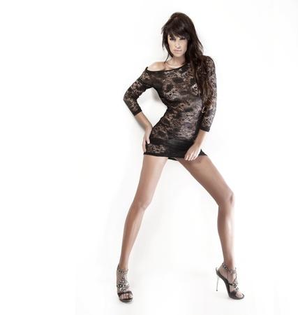 Pretty brunette Dame mit schönen Beinen in kurzen schwarzen Kleid und posiert auf weißem Hintergrund Standard-Bild - 17336889
