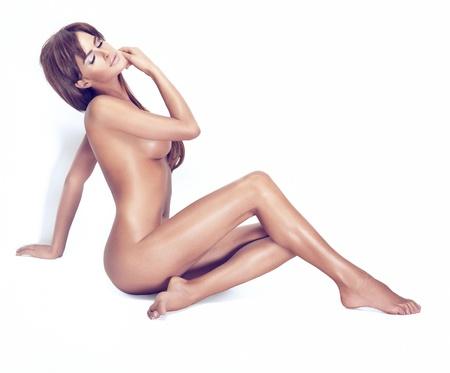 donna completamente nuda: Attraente bellezza bruna con la pelle pulita, seduta alla luce di sole Archivio Fotografico