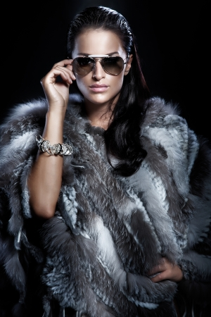 Beautiful brunette lady wearing fur and sunglasses  Fashionable photo