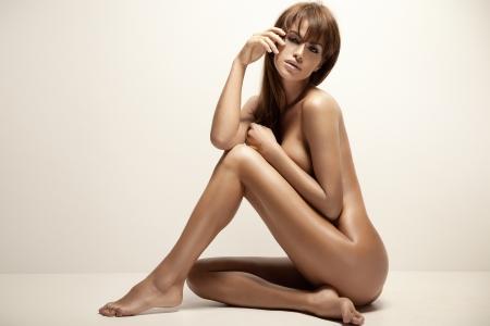 cuerpos desnudos: Joven y bella mujer se sienta sobre el fondo soleado