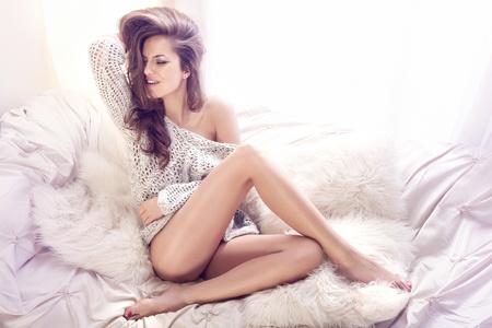 Mujer joven feliz sentado en el sofá blanco con sus hermosas piernas cruzadas