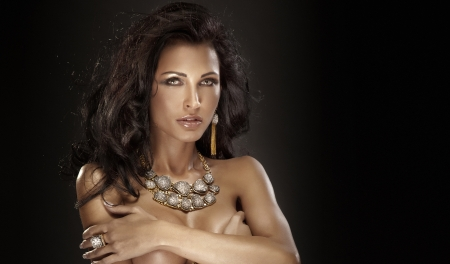 Portrait of attractive brunette woman wearing amazing gold jewelry photo