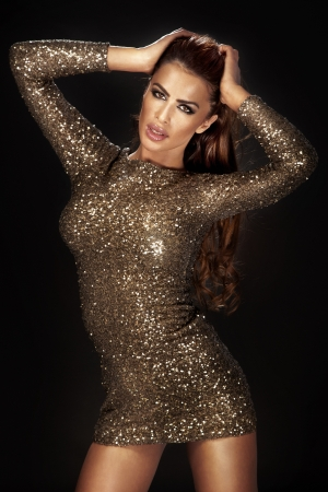 formal dress: Photo of beautiful woman dancing in gold shining dress over the black background