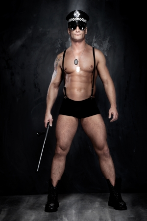 naked man: Conceptual photo of young, sexy and good looking police officer, almost naked.