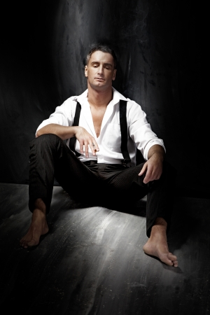 sexiness: Portrait of a handsome young man wearing white shirt and smoking while sitting on the floor
