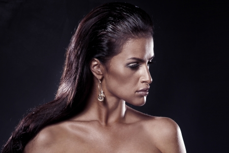 Portrait of beautiful sad woman wearing earrings. Over black background Stock Photo - 17799067