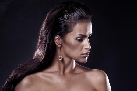 Portrait of beautiful sad woman wearing earrings. Over black background Stock Photo - 17799067