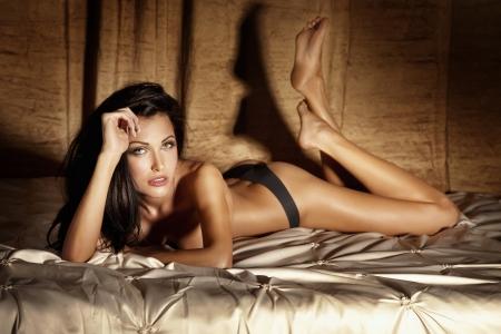 femme sous vetements: Photo de jeune femme brune sexy en lingerie pose dans le lit, se détendre