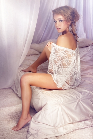 Beautiful blonde young lady sitting on the bed in lace clothes, delicate style