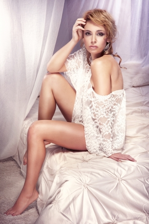 Sensual, delicate young girl sitting on the bed and posing in lace clothes photo