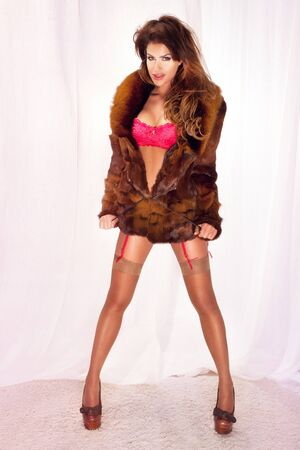 Beautiful young sexy girl standing in brown fur and red lingerie photo