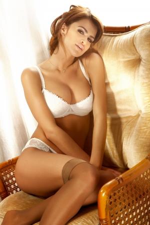 bragas: una mujer pelirroja joven y sexy en lencería blanca sentado y mirando a cámara