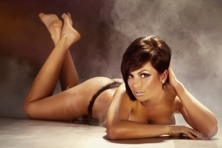 beautiful sexy young brunette woman lying on the floor, looking at camera. Naked. Tanned perfect skin.