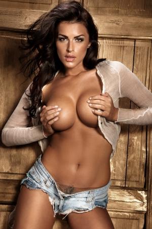 seni: Bella sexy topless donna dalla carnagione scura in posa con la sua mano che copre il seno guardando macchina fotografica lungo i capelli ricci