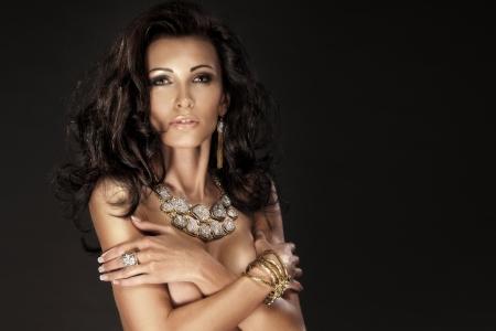 Portrait of wonderful brunette lady looking at camera wearing amazing jewellery. Stock Photo - 18299643