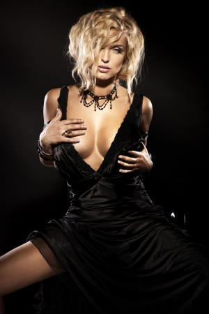 breast sexy: Sexy photo of beautiful blonde girl wearing black dress and necklace, looking at camera. Curly hair.