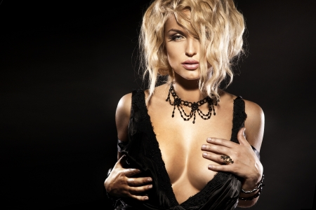 Portrait of sexy blonde woman with beautiful breast and amazing hairstyle looking at camera. Black background.