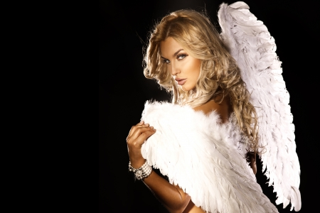 Portrait of beautiful blonde woman with angels wings. Angel with long curly hair.