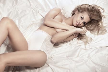modelo desnuda: Sexy mujer sonriente relaja en la cama que cubre su pecho.