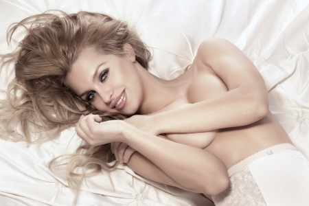 naked woman breasts: Portrait of beautiful happy young girl lying in bed covering her breast. Long curly blonde hair, amazing makeup. Stock Photo