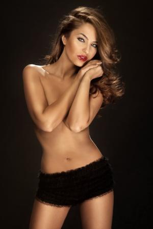 mujeres eroticas: Foto de moda de mujer sexy con labios largo rizado pelo rojo y vistiendo ropa interior negro cubriendo su pecho.