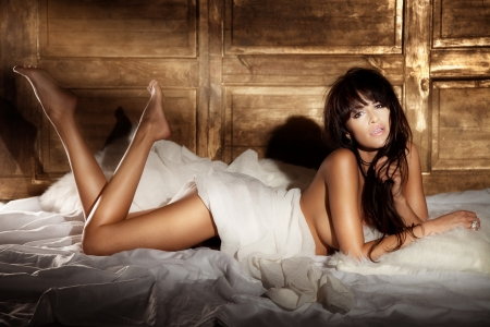 Photo of beautiful brunette woman with fringe looking at camera lying in big white bed and relaxing