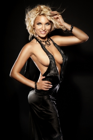 Beautiful blonde woman posing in black sexy dress, looking at camera. Curly hair. Amazing smile.  Stock Photo