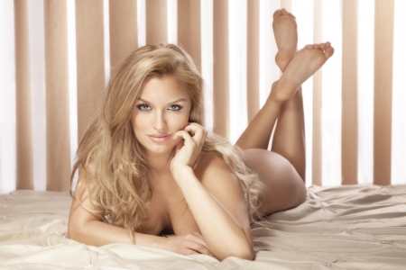 nude blonde girl: Photo of beautiful sexy woman lying on bed, looking at camera. Long curly blonde hair. Perfect body. Stock Photo