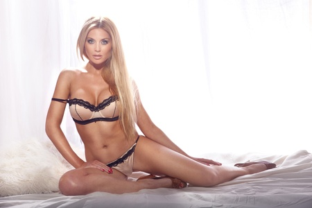 Full-length portrait of beautiful young blonde woman in sexy lingerie sitting on white bed. Long hair. Looking at camera. Stock Photo