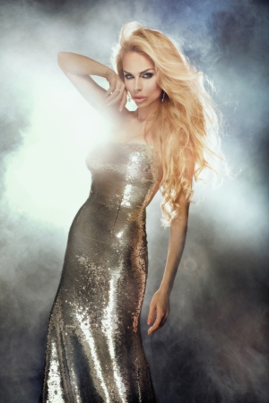 avantegarde: Fashionable photo of beautiful blonde sexy girl with long curly hair wearing silver shining dress, looking at camera. Stock Photo