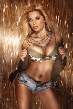 Beautiful sexy woman posing wearing jeans short and bra  Long healthy blonde hair   photo