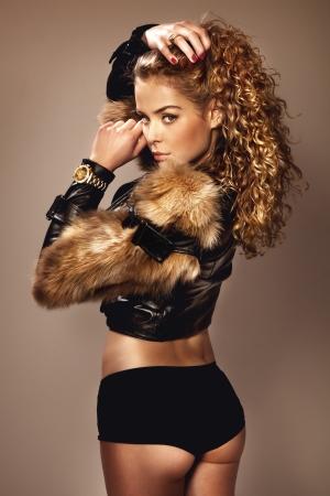 chaqueta de cuero: Mujer hermosa joven con el pelo largo y rizado posando en pieles de moda y ropa interior negro Foto de archivo
