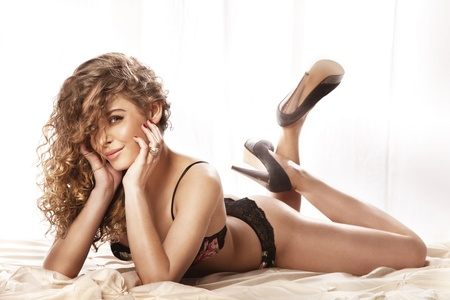 girl lying studio: Cheerful sexy girl with curly hair wearing lingerie lying in bed, looking at camera and smiling
