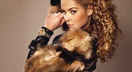 Portrait of beautiful young girl wearing fashionable fur and watch, looking at camera