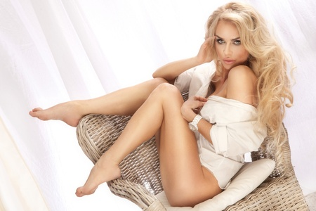 sexy lingerie:   sexy beautiful woman sitting on chair, relaxing, wearing white shirt  Looking at camera  Blonde long curly hair  Stock Photo