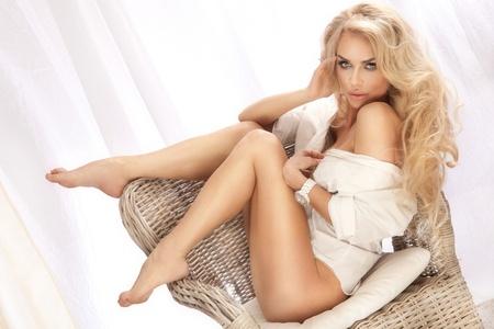 femme en lingerie: sexy belle femme assise sur une chaise, se d�tendre, v�tu d'une chemise blanche regardant la cam�ra cheveux blonds longs et boucl�s