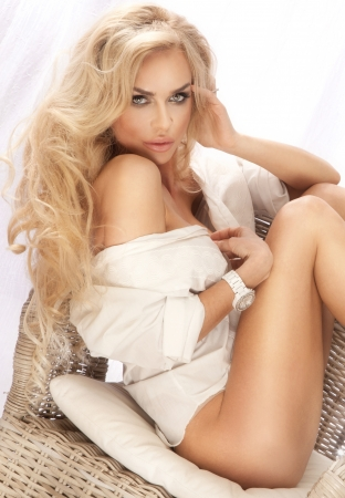 Portrait of cute blonde woman wearing white shirt, relaxing  Long curly hair