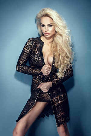Beautiful blonde sexy lady posing in black fashionable dress  Looking at camera  Long curly hair Stock Photo - 18634023
