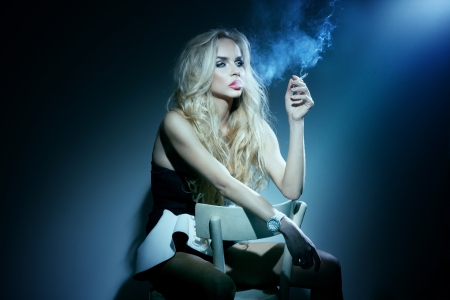 sexy girl smoking: Conceptual photo of fashionable woman sitting with cigarette in hand, looking away.A lot of smoke.