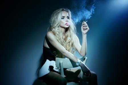 Konzeptionelle Foto von modischen Frau sitzt mit Zigarette in der Hand, auf der Suche away.A viel Rauch. Standard-Bild - 18630882