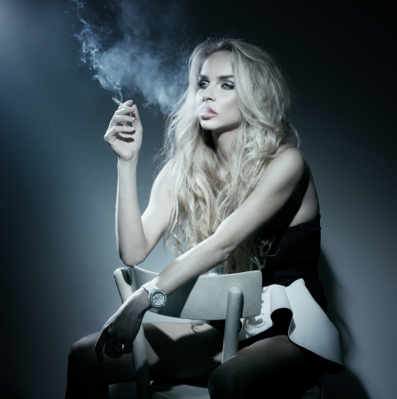 Beautiful young blonde woman smoking a cigarette, thinking. Looking away. photo