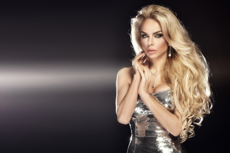 Fashion picture of beautiful young blonde woman wearing glitter silver dress. Long healthy curly hair.